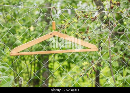 Cintres en métal accroché à une clôture métallique sur fond de verts dans un village Banque D'Images