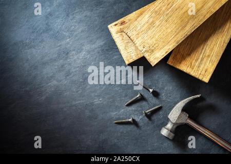 Marteau et du bois sur fond de ciment noir. Vue de dessus et copiez l'espace pour le texte. Concept de carpenter ou de construire. Banque D'Images