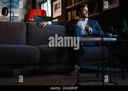 Handsome young man holding Coffee cup assis sur le canapé dans office