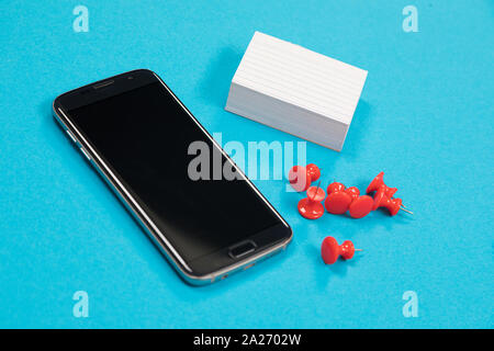 Téléphone portable noir, une pile de papier brouillon blanc et rouge sont les broches se trouvant sur la surface bleu pâle isolated Banque D'Images