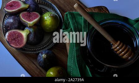 Vue d'en haut. Violet et Vert frais figues sur un bol en métal et accompagnée d'un pot de miel. Fond bleu, Banque D'Images