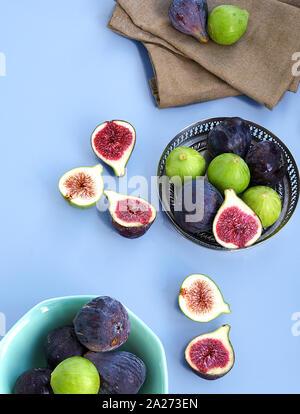 Violet et Vert frais figues sur un bol en métal et sur un fond bleu. Banque D'Images
