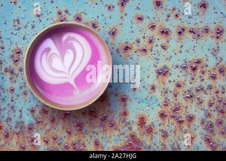 Betterave rouge super latte dans du papier craft tasse jetable, vue du dessus sur la surface de métal rouillé Banque D'Images