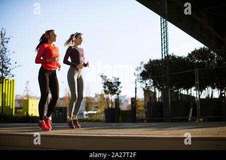 Décor de deux femmes joggers poursuivant leur activité en plein air en milieu urbain Banque D'Images