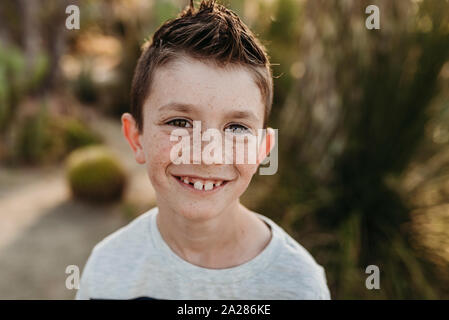 Close up portrait of young boy with freckles smiling