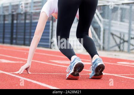 Une femelle high school sprinter est dans le 'set' position sur une piste rouge Banque D'Images
