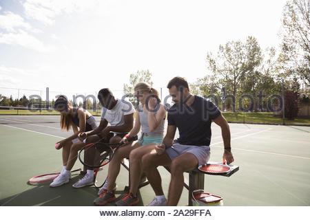 Les jeunes couples se préparant à jouer au tennis sur banc de tennis ensoleillée Banque D'Images