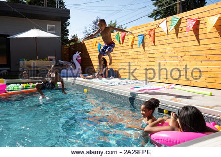 Frères espiègles sautant à sunny, piscine d'été Banque D'Images