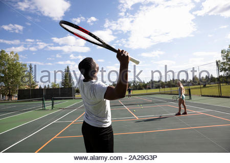 Jeune homme au service de la balle, jouant des couples tennis sur court de tennis ensoleillé Banque D'Images