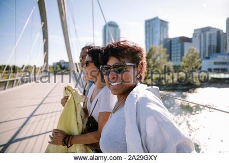 Portrait souriant, confiant mature woman avec des amis sur sunny, pont urbain Banque D'Images