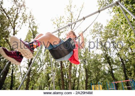 Candid portrait of young girl on swing en été Banque D'Images