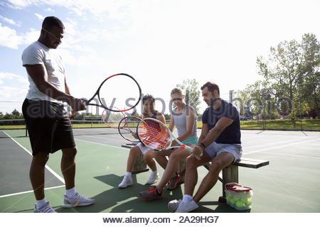 Jeune homme amis enseignement comment grip raquette de tennis sur le court de tennis ensoleillé Banque D'Images
