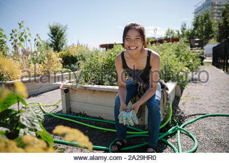 Portrait of happy young woman gardening in sunny jardin communautaire Banque D'Images