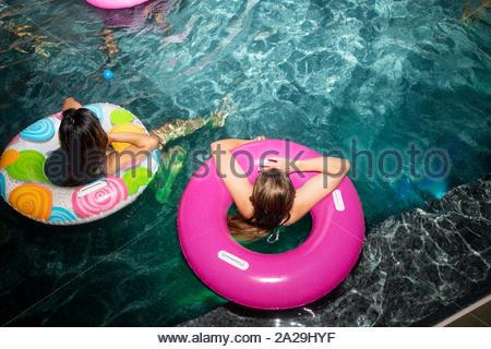 Vue de dessus les jeunes femmes amis en anneaux Gonflables de piscine d'été de nuit Banque D'Images