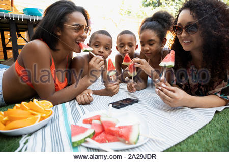 Carefree family eating watermelon sur couverture en herbe de l'été Banque D'Images