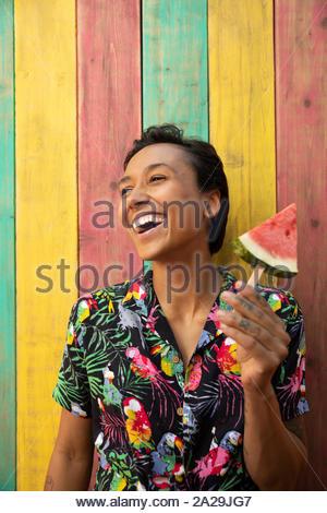 Carefree Portrait young woman eating watermelon slice sur patio d'été Banque D'Images