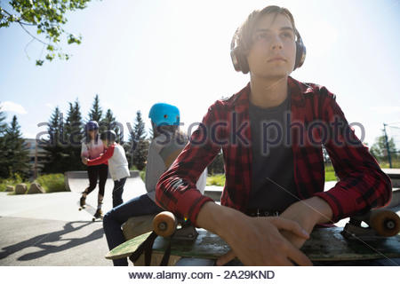 Thoughtful girl skateboard avec l'écoute de la musique avec des écouteurs à sunny skate park Banque D'Images