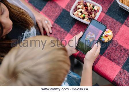 Photographier la nourriture au garçon sur smartphone pique-nique Banque D'Images