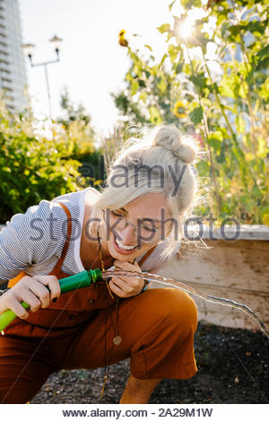 Happy young woman drinking from flexible dans sunny jardin communautaire Banque D'Images