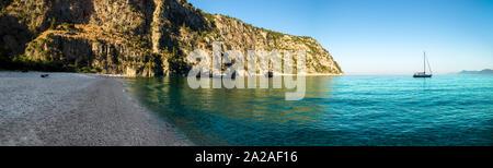 La voile des bateaux amarrés dans une plage isolée au lever du soleil Banque D'Images