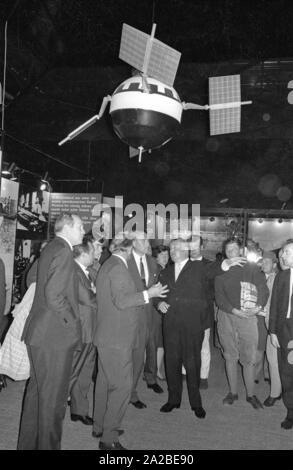 L'ingénieur Wernher von Braun (4e à partir de la droite, 1er rang) visite le Salon International des Transports (IVA) sur le parc des expositions de Theresienhöhe à Munich. Au-dessus de lui, c'est un satellite. Banque D'Images