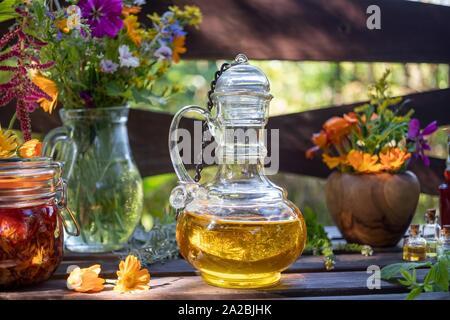 Bouteilles d'huiles essentielles et de plantes, avec des plantes médicinales et des fleurs à l'arrière-plan. Banque D'Images