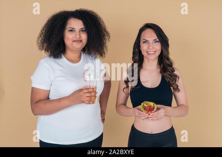 Une fille mince avec un gâteau dans les mains et une grosse fille avec une alimentation cocktail. Régime alimentaire sain. Une mauvaise alimentation Banque D'Images