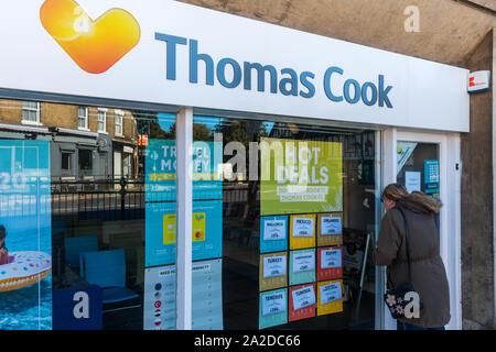 Ancien Thomas Cook Travel store, Biggleswade High Street, malheureuse femme à la clientèle dans le cadre de fenêtre fermé boutique. Banque D'Images