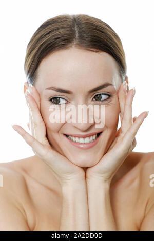 Jolie jeune femme, berçant sa tête avec ses mains en riant
