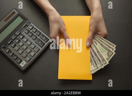 Notion de salaire ou de pot-de-vin pour travailler. Enveloppe jaune avec de l'argent sur une table. Banque D'Images