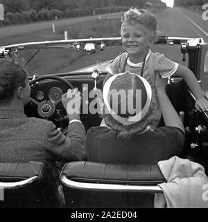 Ein kleiner Junge während der Fahrt in einem Ford V8 Cabrio, Deutschland 1930 er Jahre. Un petit garçon alors qu'avec une Ford V8 décapotable, Allemagne 1930. Banque D'Images