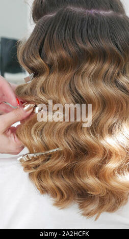Salon de mettre les mains dans un fermoir cheveux du client Banque D'Images