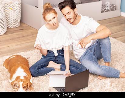 Jeune couple avec mignon chien beagle afin d'organiser une planification de la chambre des enfants. Notion de famille. Banque D'Images