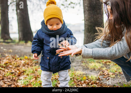 Mignon bébé garçon mode dans les tenues de explore le monde avec la mère à l'automne nature park