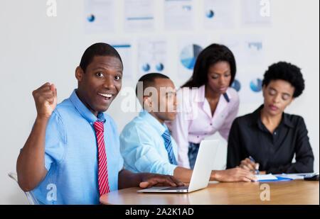 African American businessman cheering avec l'équipe d'entreprise au bureau de l'entreprise Banque D'Images