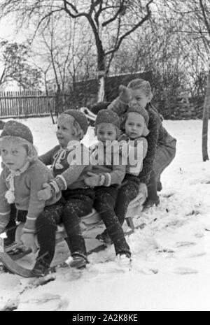 Un Schlittenfahren Weihnachten bei einer Familie mit Vierlingen, 1930er Jahre Deutschland. Équitation un traîneau à Noël à une famille de quadruplés, filles Allemagne 1930. Banque D'Images