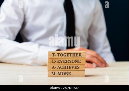 Team - Ensemble chacun réalise plus de signer sur des chevilles en bois empilé avec portrait en arrière-plan. Banque D'Images