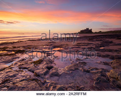 Un lever du soleil se reflète dans de beaux bassins de marée sur la plage de Bamburgh avec le célèbre château surplombant la scène sur l'horizon. Banque D'Images