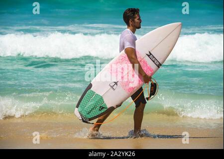 RIO DE JANEIRO - Février 9, 2017: un jeune surfeur brésilien se promène avec son surf à travers les vagues à l'Arpoador, spot de surf populaire sur Ipanema. Banque D'Images