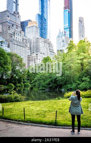 Jeune femme photographies touristiques pond et bâtiments dans Central Park, New York City, USA.
