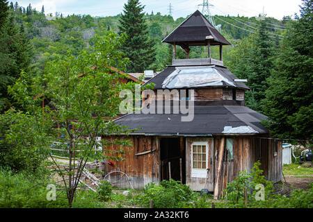 Une église en bois délabrées comme structure est vu dans un milieu rural à un défrichage camping sacrée parmi les arbres verts luxuriants avec copie espace. Banque D'Images