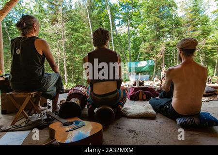 Trois hommes d'âges différents sont vus de dos, assis autour d'un camping dans une clairière dans la forêt lors d'une retraite consacrée aux cultures indigènes et chamaniques. Banque D'Images