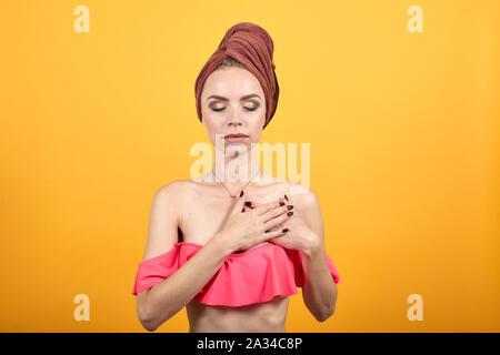Jeune fille avec une serviette sur sa tête sur fond orange isolé montre les émotions Banque D'Images