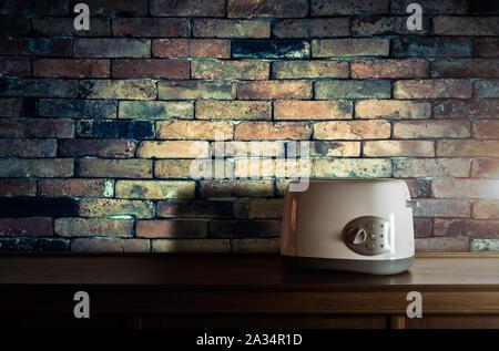 Grille-pain blanc sur armoire en bois dans la cuisine chambre avec mur de brique vintage contre lumière chaude Banque D'Images