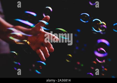 Bulles de savon coloré survolant darck contexte et la main de l'homme tryimg pour les attraper Banque D'Images