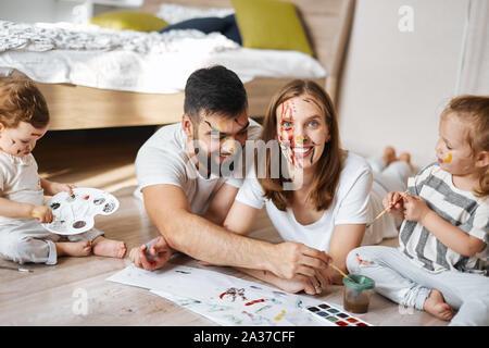 Les jeunes parents développer leurs enfants, femme heureuse avec visage peint regardant la caméra , la photo en gros plan. Banque D'Images