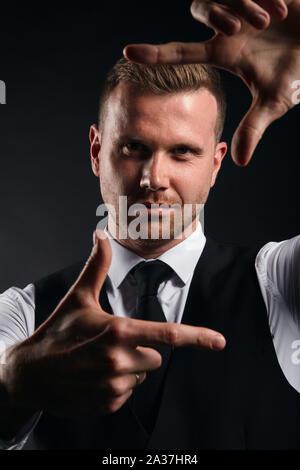 Les jeunes bel homme en chemise blanche, gilet noir qui cadre avec ses mains sur fond noir, la photo en gros plan sur fond noir isolé. Banque D'Images