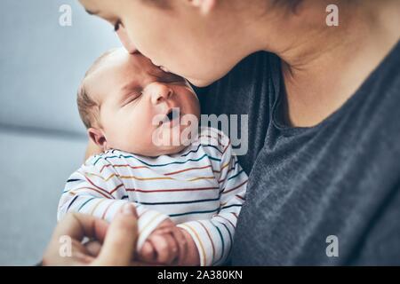 Mère avec nouveau-né. Femme l'embrassant son fils de 4 jours à la maison.