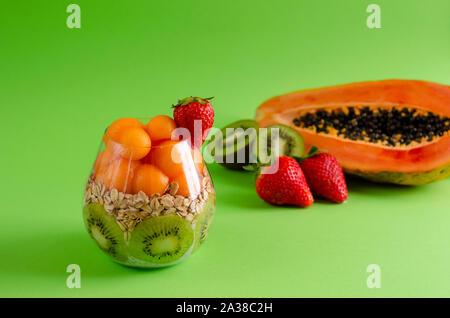 Chia pudding avec des matières premières fraîches de fruits tropicaux, de flocons d'avoine pour une saine alimentation sur fond vert. Alimentation équilibrée le petit-déjeuner gratuit. Vue avant, copie savs Banque D'Images