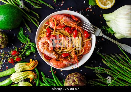 Un délicieux plat de pâtes italiennes avec tiger gambas ou crevettes et légumes frais sur fond noir. Une cuisine méditerranéenne saine et concept.